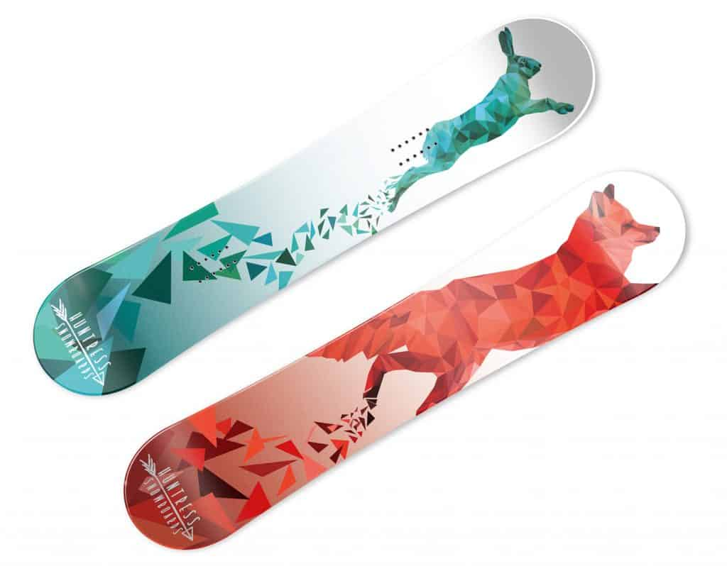 Two snowboards are seen. One has a geometric rabbit in blue and green. The other has a geometric fox in red and orange.