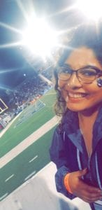 Laura is pictured in front of a football field dress up to cheer on her team.
