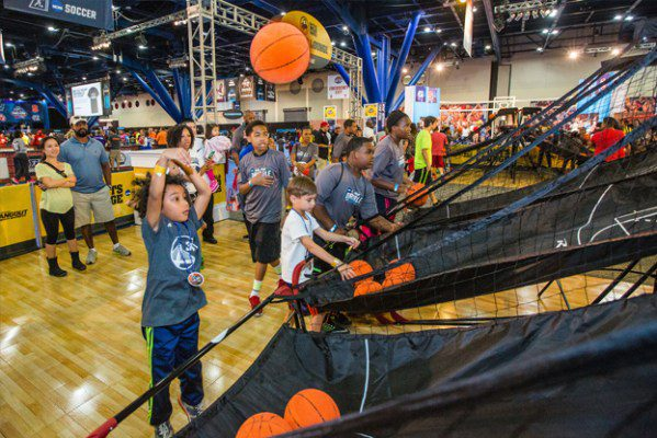 Kid tossing a basketball into the air at a tradeshow logistics expo