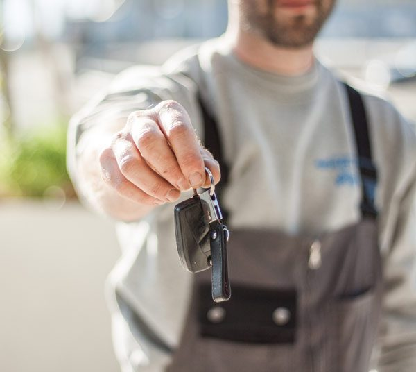 out-of-focus mechanic wearing grey overalls handing car key chain with fob