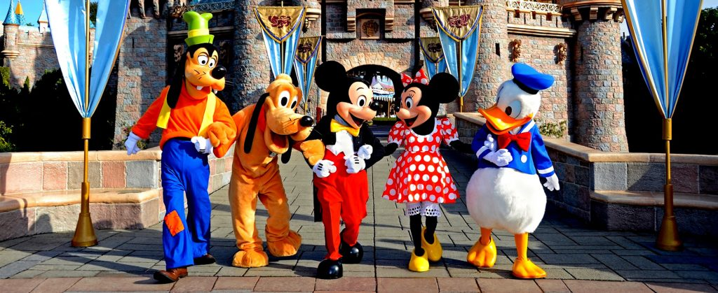Disney characters linking arms and laughing in front of Disneyland castle from left to right: Goofy, Pluto, Mickey, Minnie, and Donald Duck