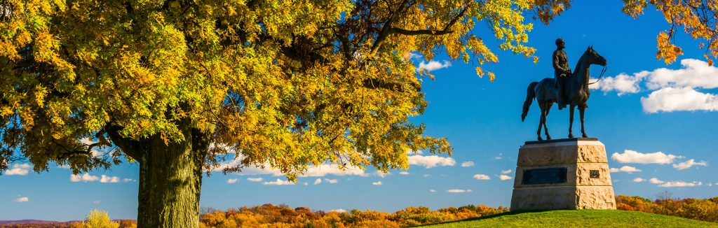Large green and orange tree in the fall hanging over black statue in Gettysburg National Military Park