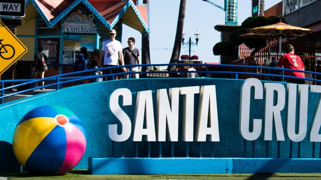 White Santa Cruz Beach sign with 1 beach ball on the left and 2 beach balls on the right of sign, northern california graduation trips