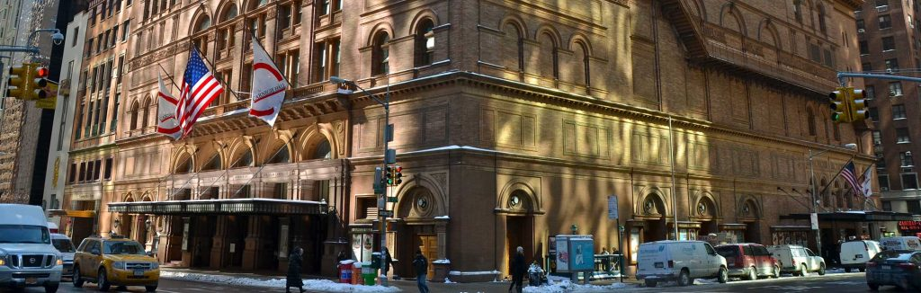 Carnegie Concert Hall in Manhattan, New York with snow on the sidewalk and cars on the streets, carnegie hall performance tours