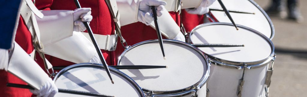 Educational Discovery Performance Tour drumline in red and white uniforms holding black drum sticks playing white drums, parades bowl games and festival tours