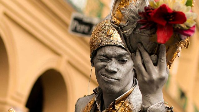 New Orleans street performer in gray body paint and gold costume holding flowers, new orleans performance tours
