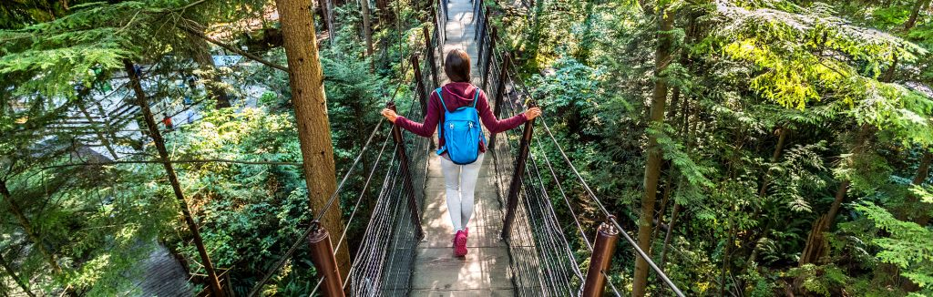 Girl dress in maroon jacket, white leggings, and pink shoes walking across a bridge on a hiking trail in the woods